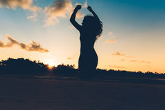 Silhouette portrait of summer girl jumping with hands in air on white sand in exotic island at sunset. Beautiful silhouette portrait of summer girl jumping with Stock Photos