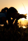 Silhouette portrait of a young woman photographing a beautiful nature at sunset on photo equipment royalty free stock image