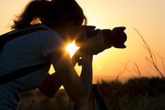 Silhouette portrait of a young woman photographing a beautiful nature at sunset on photo equipment Stock Image