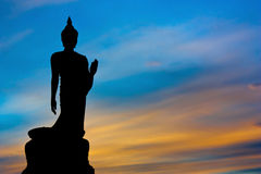 Silhouette Of The Posture Of Walking Buddhist Statue In Twilight Stock Photos