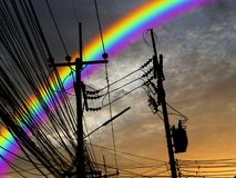 Silhouette power electric line rainbow in sunset sky. Silhouette  of power electric line and rainbow in sunset sky Royalty Free Stock Photo