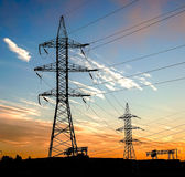 Silhouette of power lines in the factory and sunset background Royalty Free Stock Photo