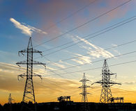 Silhouette of power lines in the factory and sunset background Royalty Free Stock Image