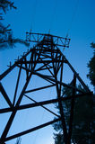Silhouette of a power transmission line tower. Against the blue sky in the forest stock image