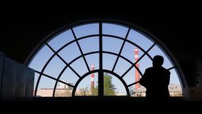 Silhouette of a powerful dominating male looking out a glass window over the city in contemplation or reflection. Rear. Stylish business man in the background of Stock Photos
