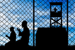 Silhouette pray refugee camp. Concept of security. Silhouette of praying refugees and barbed wire fence on the background of the observation tower and stalls Royalty Free Stock Image