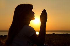 Silhouette of a praying girl at  sunset Stock Image