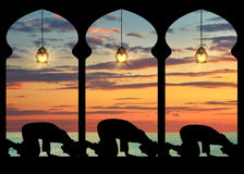 Silhouette of praying Muslims. Concept of the Islamic religion. Silhouette of praying Muslims in the background of the sea sunset Stock Photo