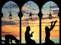Silhouette of praying Muslims. Concept of the Islamic religion. Silhouette of praying Muslims in the background of the sea sunset Royalty Free Stock Photos