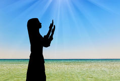 Silhouette of praying woman Stock Photo