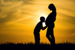 Silhouette pregnant and her son. Silhouette pregnant woman and her son stock image
