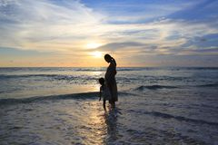 Silhouette Pregnant mother and daughter relaxing on the beach at sunset royalty free stock photos