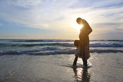 Silhouette Pregnant mother and daughter relaxing on the beach at sunset stock photo