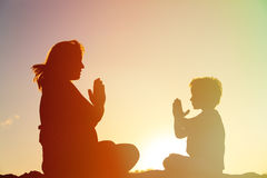 Silhouette of pregnant mother and son doing yoga on beach Stock Images