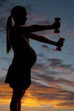 Silhouette pregnant with weights Royalty Free Stock Image