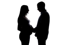 Silhouette pregnant wife and husband holding hands. Silhouette of pregnant wife and husband holding hands on white background stock photo