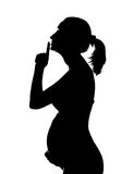 Silhouette of pregnant woman. Holding abdomen and showing SHH sign royalty free stock photography