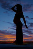 Silhouette pregnant woman arm on head one behind Stock Image