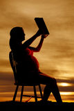 Silhouette pregnant woman in chair reading a book Stock Photo