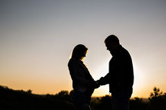 Silhouette of a pregnant woman with husband in sunset Stock Image