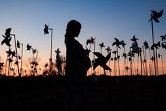 silhouette of pregnant woman in the middle of pinwheel field royalty free stock photography