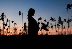 silhouette of pregnant woman in the middle of pinwheel field stock photography