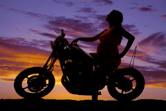 Silhouette pregnant woman on motorcycle side hand on tank. A silhouette of a pregnant woman sitting on her motorcycle looking up stock image