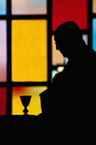 Silhouette of priest. Silhouette of a priest during catholic mass Stock Photo