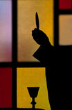 Silhouette of priest lifting host Royalty Free Stock Image