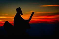 Silhouette of priest reading in the sunset light Royalty Free Stock Photos