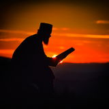 Silhouette of priest reading in the sunset light Royalty Free Stock Image