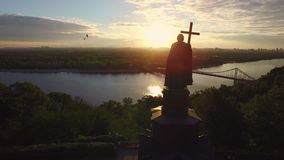 Silhouette Prince Vladimir with christian cross in Kiev city on sunset landscape. Aerial view monument Prince Vladimir with cross in hand on evening city stock video