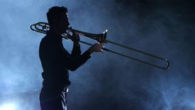 Silhouette professional musician man playing on trumpet. Smoky isolated studio stock video