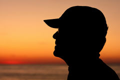 Silhouette profile of man wearing baseball cap Stock Image