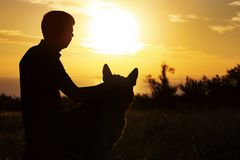 Silhouette profile of a young man and a dog watching the sun set on the horizon in a field, boy fondle his pet on nature, concept. Of emotional health in royalty free stock photo