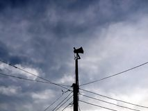 Silhouette of Public Audio Speaker and Electrical Wires in Blue Cloudy Sky. Silhouette of Public Audio Speaker for News and Information Broadcasting and Stock Images