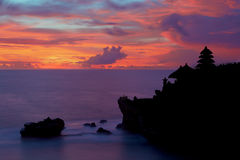 Silhouette of Pura Tanah Lot at coloured sunset. Stock Images