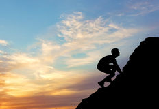 Silhouette purposeful man rising to the top of the mountain without insurance Royalty Free Stock Photos