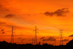 Silhouette pylons against sunset twilight zone. Silhouette electric power supply pylons in beautiful orange sunset Royalty Free Stock Photo