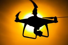 Silhouette of a quadcopter drone. Silhouette quadcopter drone phantom sunset propellar camera ariel photography royalty free stock image