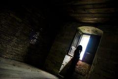 Silhouette rétro-éclairée de femme dans une fenêtre Image libre de droits
