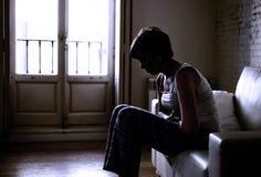 Silhouette rétro-éclairée de jeune femme se tenant blessant la crampe d'estomac de ventre et la douleur de souffrance de période photographie stock libre de droits