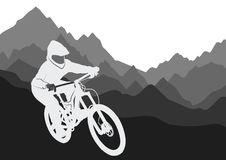 Silhouette of a racer descending on a bicycle on a mountainside.  Stock Images