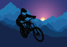 Silhouette of a racer descending on a bicycle on a mountainside against the background of the evening sun. Vector Royalty Free Stock Images