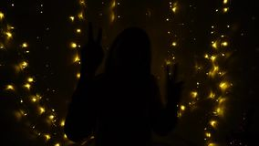 Euphoric girl dancing in the dark. Silhouette of raving young person in dark with sparkling garlands on background. Happy teenager at party showing thumbs up stock video