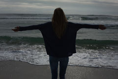 Silhouette rear view of woman with arms outstretched at beach Royalty Free Stock Photo