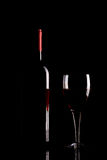 Silhouette of red wine bottle and glass on black background. Studio shot of red wine bottle and glass isolated on black background Stock Photo