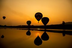 Hot air balloon in senset. Silhouette and reflection of hot air balloon going up in the sky when sunset Royalty Free Stock Images