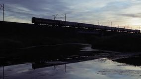 Silhouette And Reflection Of Train Crossing Bridge On Sunset