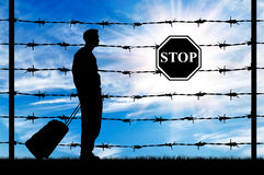 Silhouette of a refugee with a bag. Concept of refugee. Silhouette of a refugee with a bag on a background of a fence with barbed wire and stop sign Stock Image